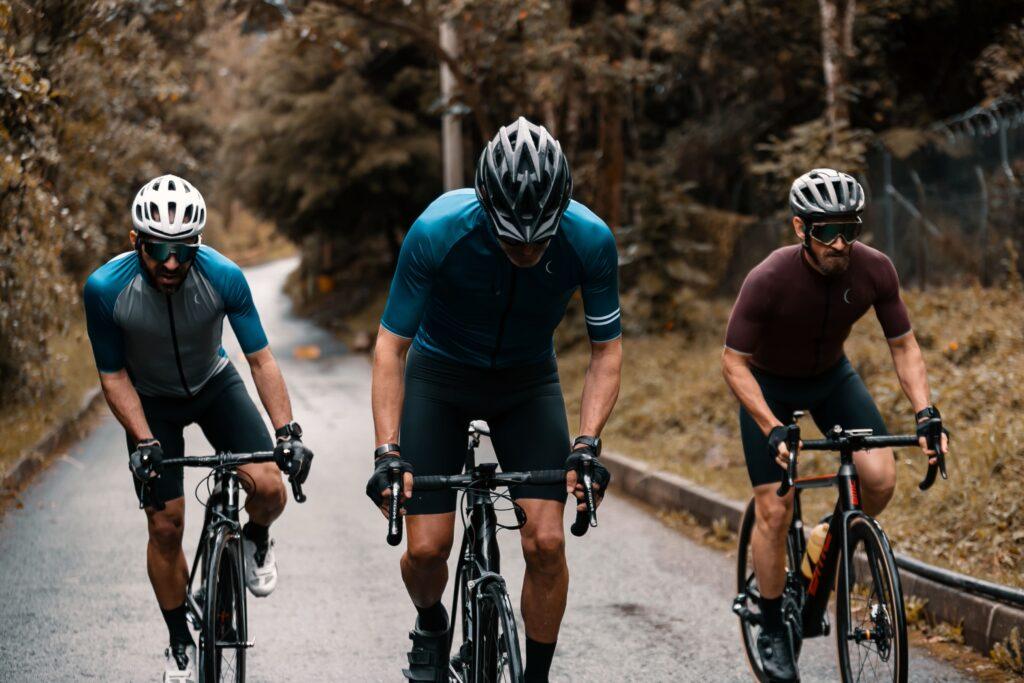 Cicliștii străbat șoseaua alături de bicicletele sale